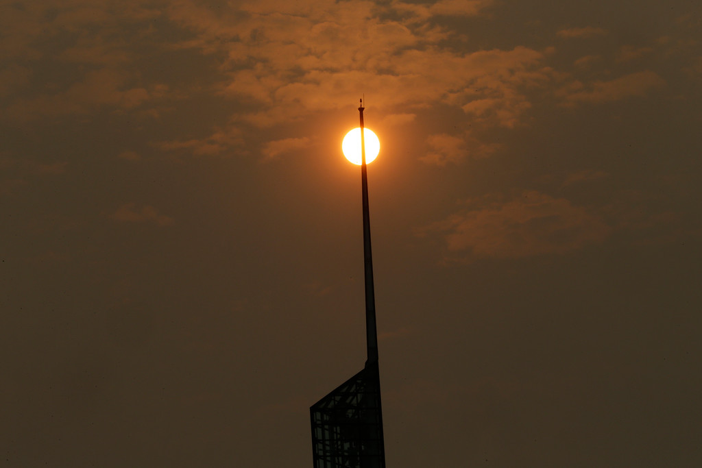 . A glowing, orange sun, muted by wildfire smoke, is visible behind the spire of the Oregon Convention Center in Portland, Ore., Tuesday, Sept. 5, 2017. The dozens of fires burning across the Western United States and Canada have blanketed the air with choking smoke from Oregon to Colorado, where health officials issued an air quality advisory alert. (AP Photo/Don Ryan)