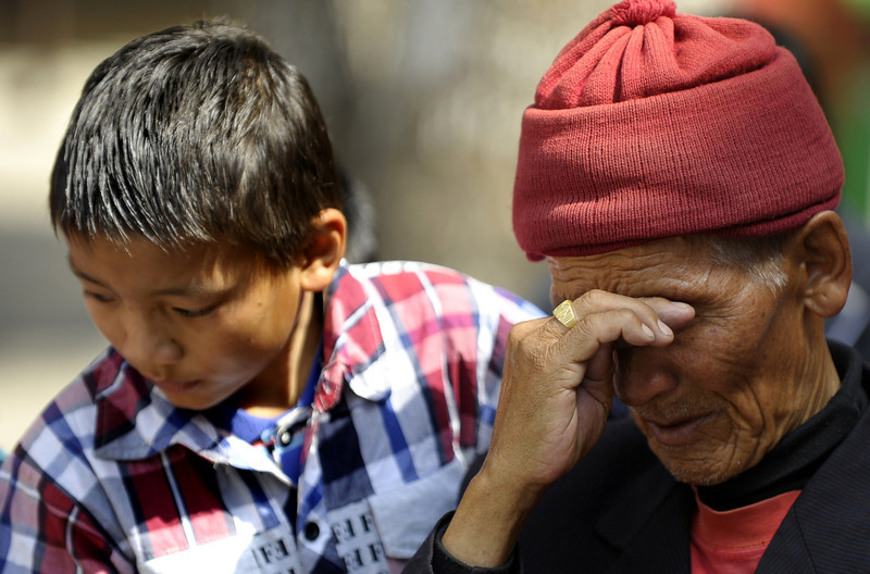 . The father (R) and son of Mount Everest avalanche victim Ang Kazi Sherpa comfort each other as they wait for his body to arrive at Sherpa Monastery in Kathmandu on April 19, 2014.  Rescuers searched Mount Everest for bodies as authorities ruled out hope of finding any more survivors from an avalanche that killed at least 12 Nepalese guides in the deadliest accident ever on the world\'s highest peak.   (PRAKASH MATHEMA/AFP/Getty Images)
