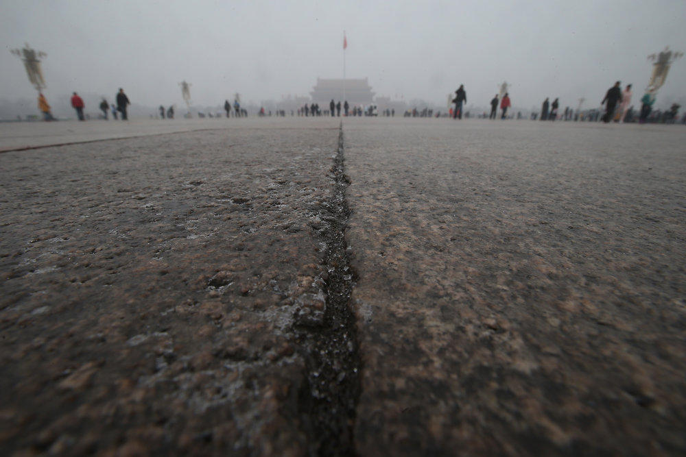 Description of . Tourists walk on the Tiananmen Square during severe pollution on January 31, 2013 in Beijing, China. Heavy smog that has choked Beijing for the last five days weakened slightly on Thursday due to a light rainfall, although the capital\'s air remains heavily polluted. The haze choking many Chinese cities covers a total area of 1.43 million square kilometers, the China\'s Ministry of Environmental Protection said Wednesday.  (Photo by Feng Li/Getty Images)