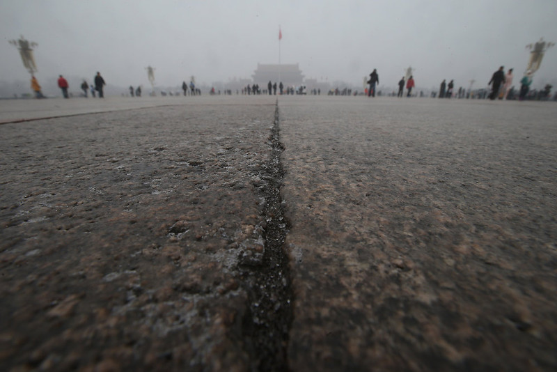 . Tourists walk on the Tiananmen Square during severe pollution on January 31, 2013 in Beijing, China. Heavy smog that has choked Beijing for the last five days weakened slightly on Thursday due to a light rainfall, although the capital\'s air remains heavily polluted. The haze choking many Chinese cities covers a total area of 1.43 million square kilometers, the China\'s Ministry of Environmental Protection said Wednesday.  (Photo by Feng Li/Getty Images)