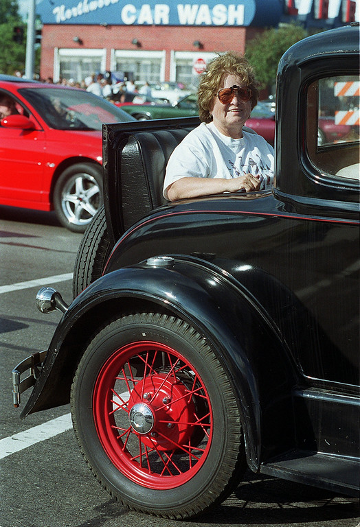 . Arbie Phillips smiles from the rumble seat of this 1930 Model A as she heads south on Woodward during the Dream Cruise 2000 saturday afternoon.