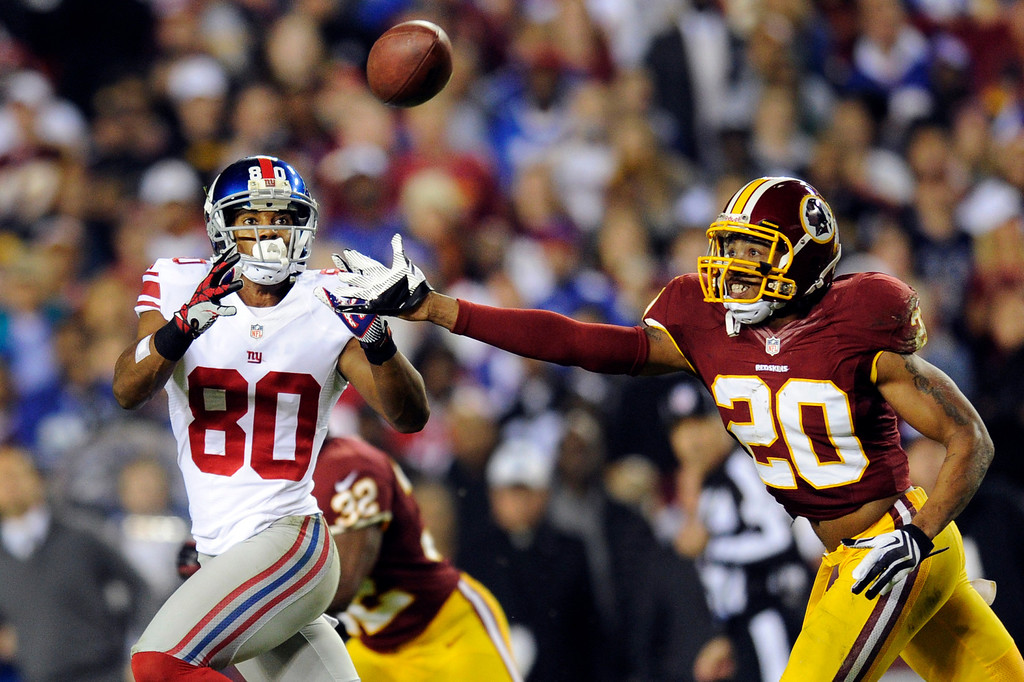 . New York Giants wide receiver Victor Cruz (80) pulls in a pass under pressure from Washington Redskins defensive back Cedric Griffin (20) during the first half of an NFL football game in Landover, Md., Monday, Dec. 3, 2012. (AP Photo/Nick Wass)