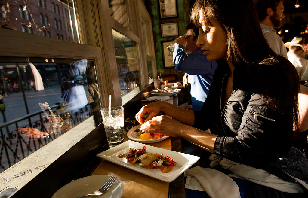. Lena El-Senussi basks in the late afternoon sunlight as she enjoys seafood  during happy hour at Jax Fish House and Oyster Bar  in downtown Denver on Friday, February 26, 2016. The Jax happy hours is all about the seafood.   (Photo by Cyrus McCrimmon/ The Denver Post)