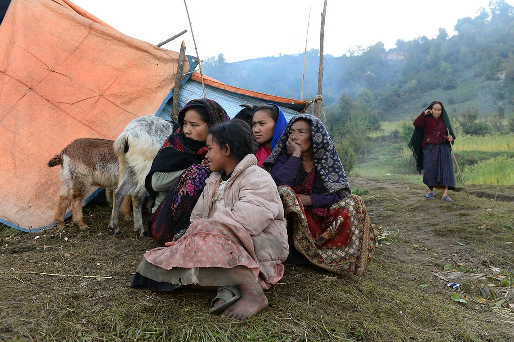 . A Nepalese family sit outside makeshift tents at Laprak village, in northern-central Gorkha district on April 30, 2015.  The UN launched an appeal for Nepalese quake survivors in dire need of shelter, food and medical care April 30 as anger boiled at the government\'s inability to cope with a disaster that has killed more than 5,000 people.  AFP PHOTO / SAJJAD  HUSSAIN/AFP/Getty Images
