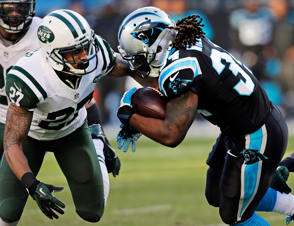 . Carolina Panthers\' DeAngelo Williams, right, is hit by New York Jets\' Dee Milliner (27) during the first half of an NFL football game in Charlotte, N.C., Sunday, Dec. 15, 2013. (AP Photo/Chuck Burton)
