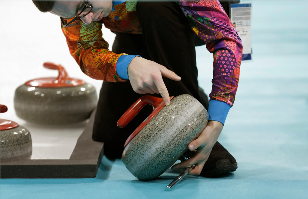 . An ice crew worker checks the surface of a curling rock at the Ice Cube Curling Center as part of preparations ahead of the 2014 Winter Olympics, Tuesday, Feb. 4, 2014, in Sochi, Russia. (AP Photo/Wong Maye-E)