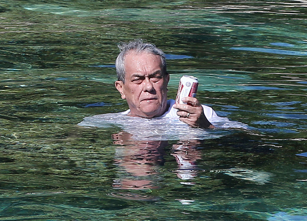 . FILE - In this Nov. 5, 2015 file photo, Marshall Islands Foreign Minister Tony de Brum cools off and relaxes with beer while he sits on a rock in Majuro Atoll, in the Marshall Islands. De Brum saw the effects of rising seas from his home in the Marshall Islands and became a leading advocate for the landmark Paris Agreement and an internationally recognized voice in the fight against global warming. De Brum died Tuesday, Aug. 22, 2017, in the capital Majuro surrounded by his family, according to Marshall Islands President Hilda Heine. He was 72.(AP Photo/Rob Griffith, File)