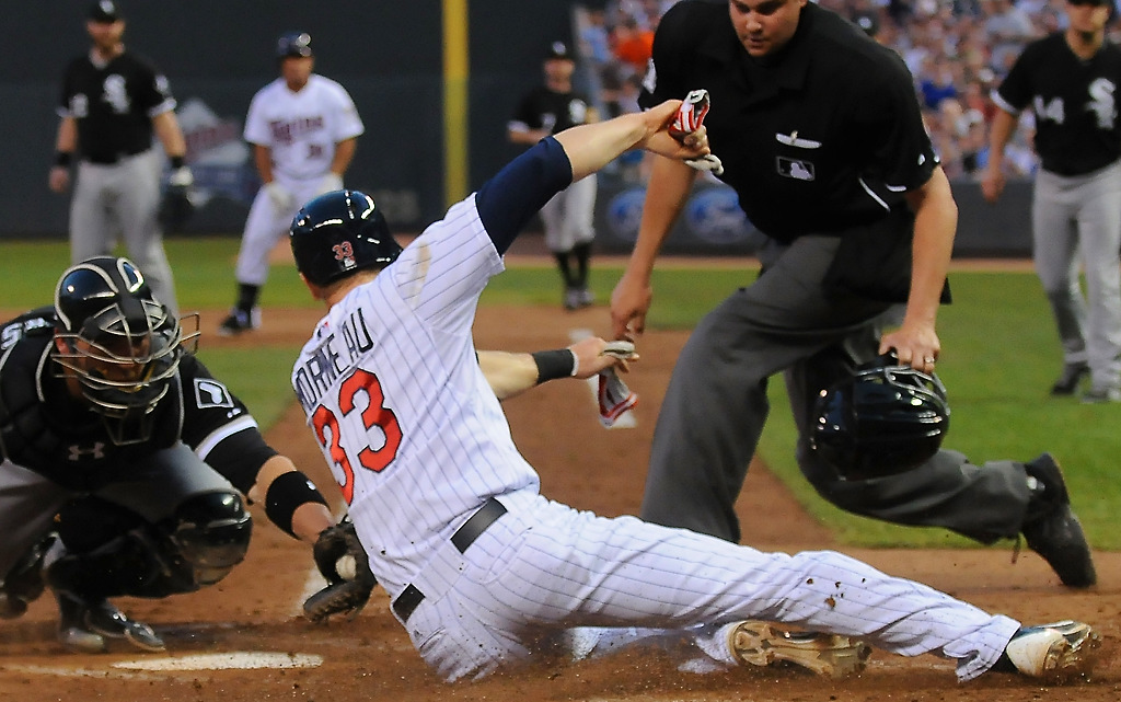 . Chicago catcher Tyler Flowers (21) misses the tag on Minnesota first baseman Justin Morneau (33) as he slides into home during the fifth inning of their game at Target Field in Minneapolis, Tuesday, May 14, 2013.  (Pioneer Press: John Autey)