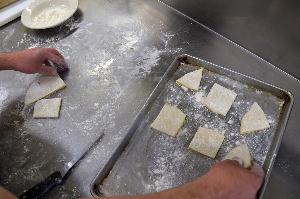 . Chef Fred Duerr places cut dough on pan.  Monday, March 3, 2014.   Photo by Geoff Patton