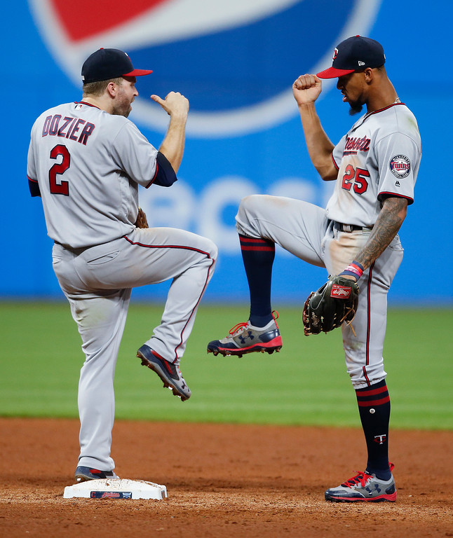 . Minnesota Twins\' Brian Dozier (2) and Byron Buxton (25) celebrate an 8-6 victory over the Cleveland Indians in a baseball game, Tuesday, Sept. 26, 2017, in Cleveland. (AP Photo/Ron Schwane)