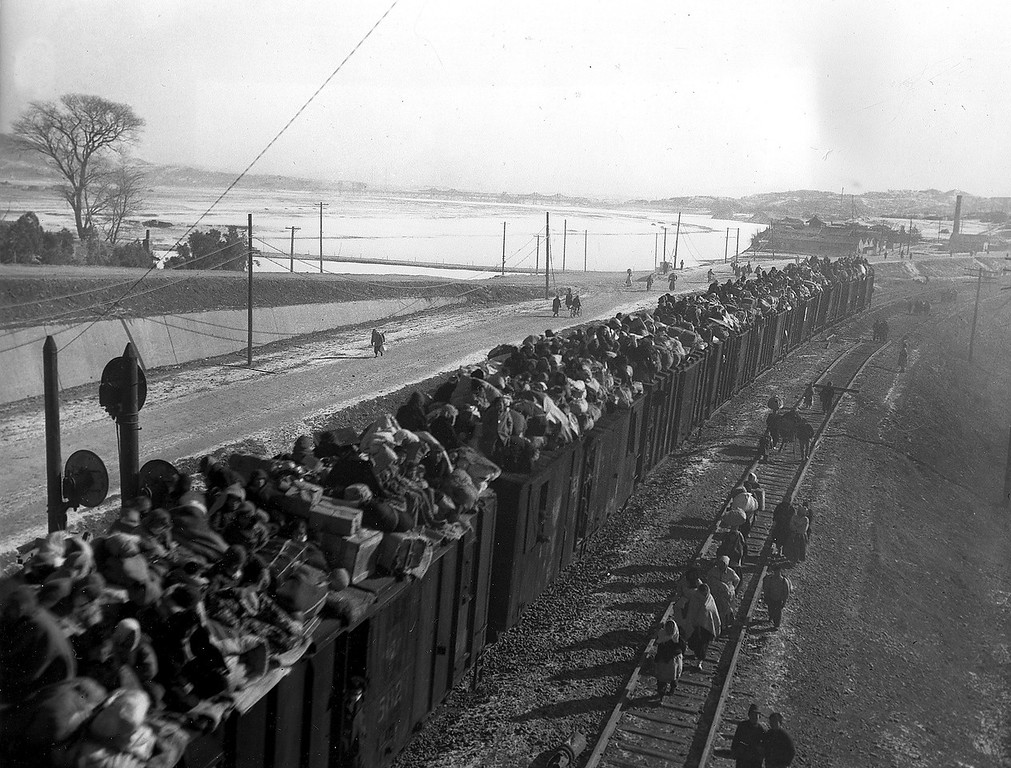 . A packed refugee train heads south through Seoul railroad yards as South Koreans continue to flee from the capital during the Korean War on Dec. 27, 1950.  More than half of the city\'s 1,000,000 residents have left the capital, threatened by massed Communist troops to the north, to seek safety in the southern part of the peninsula.  (AP Photo)
