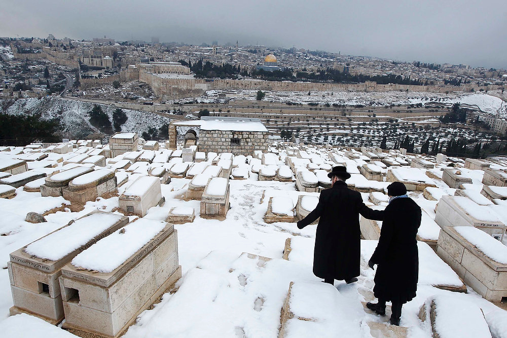 Description of . An ultra-Orthodox Jewish couple walks in a snow-covered cemetery on the Mount of Olives in Jerusalem on January 10, 2013. The worst snowstorm in 20 years shut government offices, public transport and schools in Jerusalem and along the northern Israeli region bordering on Lebanon on Thursday.  REUTERS/Baz Ratner