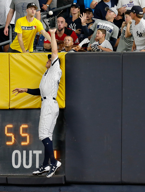 . New York Yankees right fielder Aaron Judge makes a catch at the wall on a line drive hit by Cleveland Indians\' Francisco Lindor during the sixth inning in Game 3 of baseball\'s American League Division Series, Sunday, Oct. 8, 2017, in New York. (AP Photo/Kathy Willens)