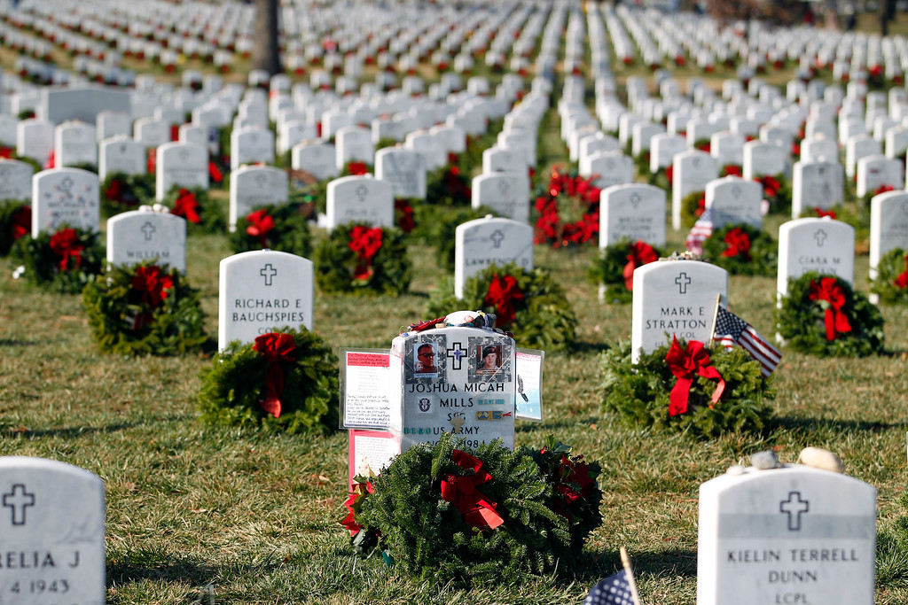 . The head stone of Army Staff Sgt. Joshua Micah Mills is decorated with a wreath and other memorials at Arlington National Cemetery in Arlington, Va., Saturday, Dec. 15, 2012, during Wreaths Across America Day. Wreaths Across America was started in 1992 at Arlington National Cemetery by Maine businessman Morrill Worcester and has expanded to hundreds of veterans\' cemeteries and other locations in all 50 states and beyond. (AP Photo/Jose Luis Magana)