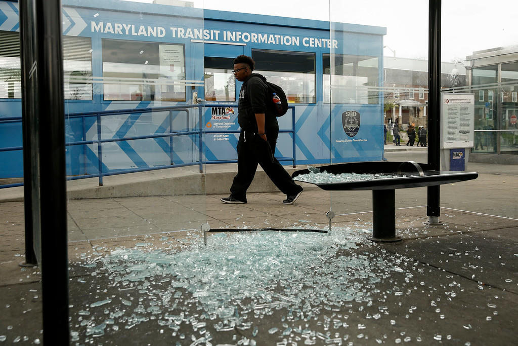 . BALTIMORE, MD - APRIL 27:  A man walks by broken glass at a bus stop near Mondawmin Mall, April 27, 2015 in Baltimore, Maryland. The funeral service for Freddie Gray, who died last week while in Baltimore Police custody, was held on Monday morning. (Photo by Drew Angerer/Getty Images)