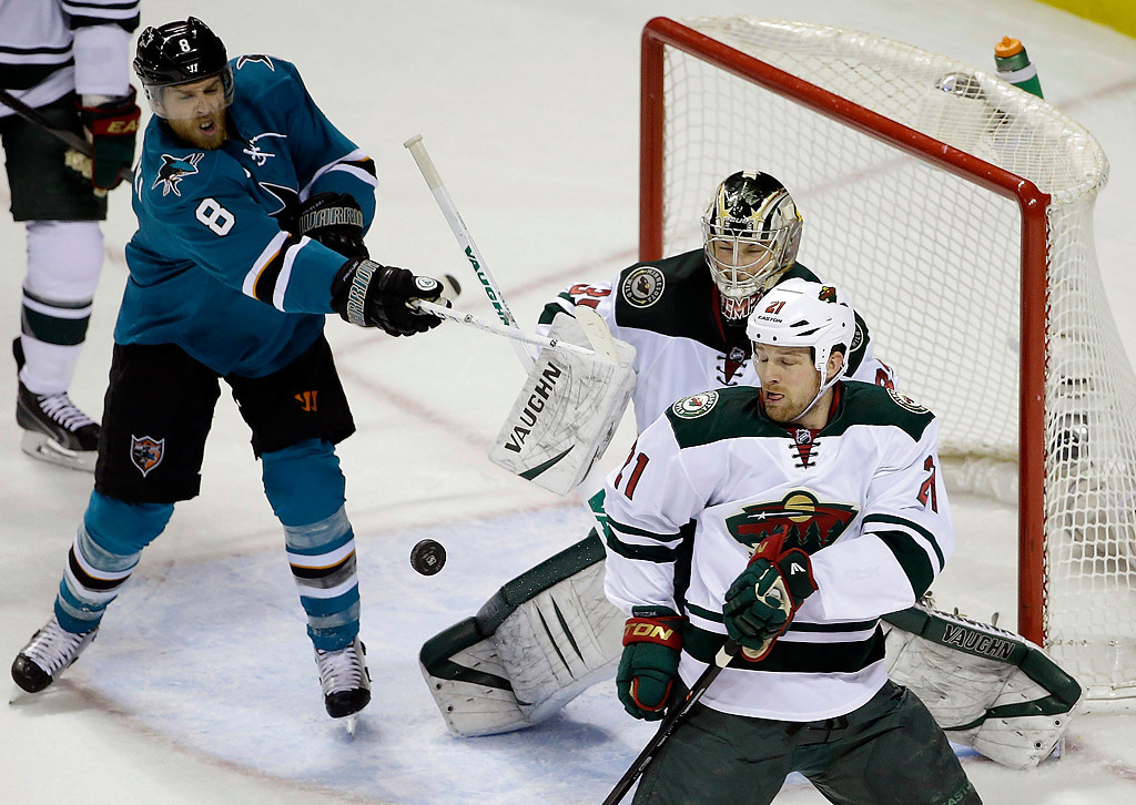 . Minnesota Wild goalie Darcy Kuemper, center, stops a shot attempt from San Jose Sharks\' Joe Pavelski (8) during the first period of an NHL hockey game on Saturday, Jan. 25, 2014, in San Jose, Calif. (AP Photo/Marcio Jose Sanchez)