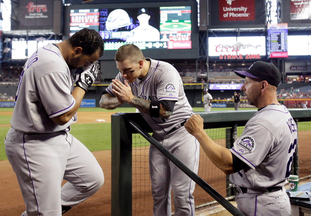 . Colorado Rockies catcher Wilin Rosario, left, celebrates with Colorado Brandon Barnes, center, and Walt Weiss, right, after hitting a solo home run against the Arizona Diamondbacks in the sixth inning during a baseball game, Sunday, Aug. 10, 2014, in Phoenix. (AP Photo/Rick Scuteri)