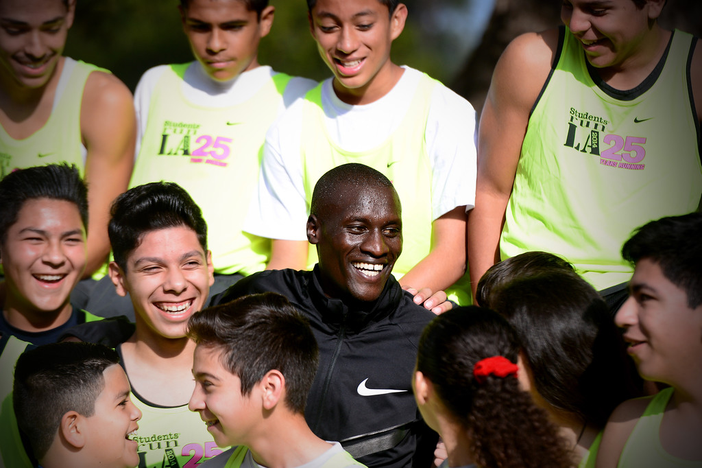 . Elite marathon runner Lani Rutto, of Kenya, joins students, of the Students Run LA program, for a group portrait while the elite athletes were training at Griffith Park in Los Angeles Friday, March 7, 2014 for the LA Marathon. The students will also be running Sunday\'s marathon.(Photo by Sarah Reingewirtz/Pasadena Star-News)