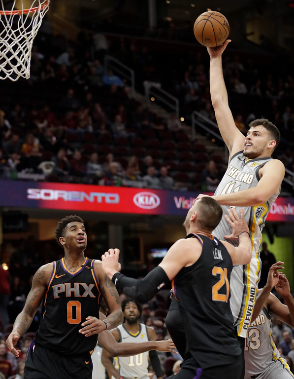. Cleveland Cavaliers\' Ante Zizic, right, shoots over Phoenix Suns\' Marquese Chriss, left, and Alex Len during the second half of an NBA basketball game Friday, March 23, 2018, in Cleveland. The Cavaliers won 120-95. (AP Photo/Tony Dejak)