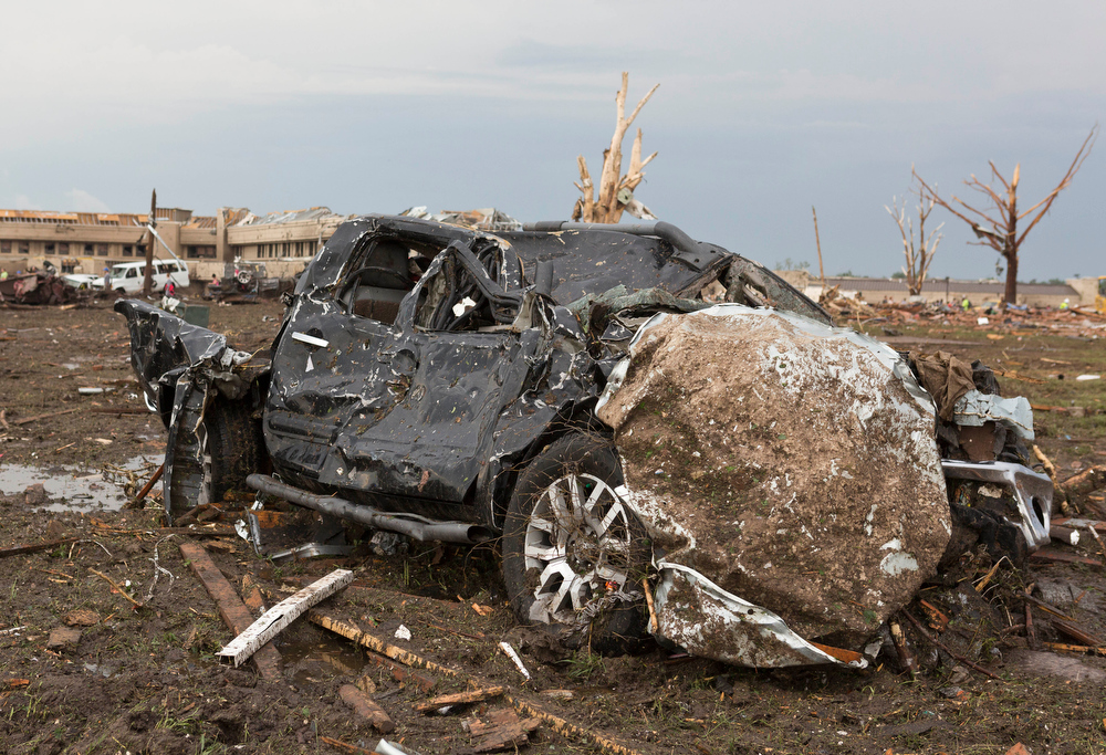 . A truck lays damaged in a field near the Moore Medical Center, background, after a tornado moves through Moore, Okla. on Monday, May 20, 2013. (AP Photo/Alonzo Adams)