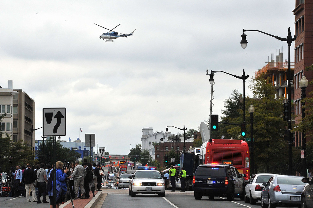 """. Media and emergency response personnel gather outside the US Navy Yard September 16, 2013 in Washington, DC. At least one unidentified gunman opened fire at the US Navy Yard in Washington on Monday and was at large after killing \""""multiple\"""" victims and wounding several more, officials said. Police and FBI agents descended on the area in force as helicopters swarmed overhead, amid reports a shooter was armed with an assault rifle and was holed up at the complex. \""""We believe there were multiple deaths,\"""" a US defense official, speaking on condition of anonymity, told AFP. The precise death toll remained unclear, the official said. A Washington DC police officer and another law enforcement officer had been shot while the gunman had allegedly barricaded himself in a room in a headquarters building, media reported.   MLADEN ANTONOV/AFP/Getty Images"""