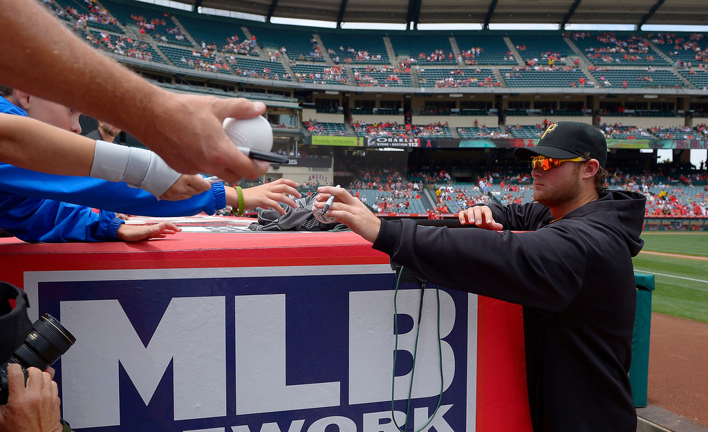 . Pittsburgh Pirates starting pitcher Gerrit Cole, right, signs autographs prior to their baseball game against the Los Angeles Angels, Sunday, June 23, 2013, in Anaheim, Calif.  (AP Photo/Mark J. Terrill)
