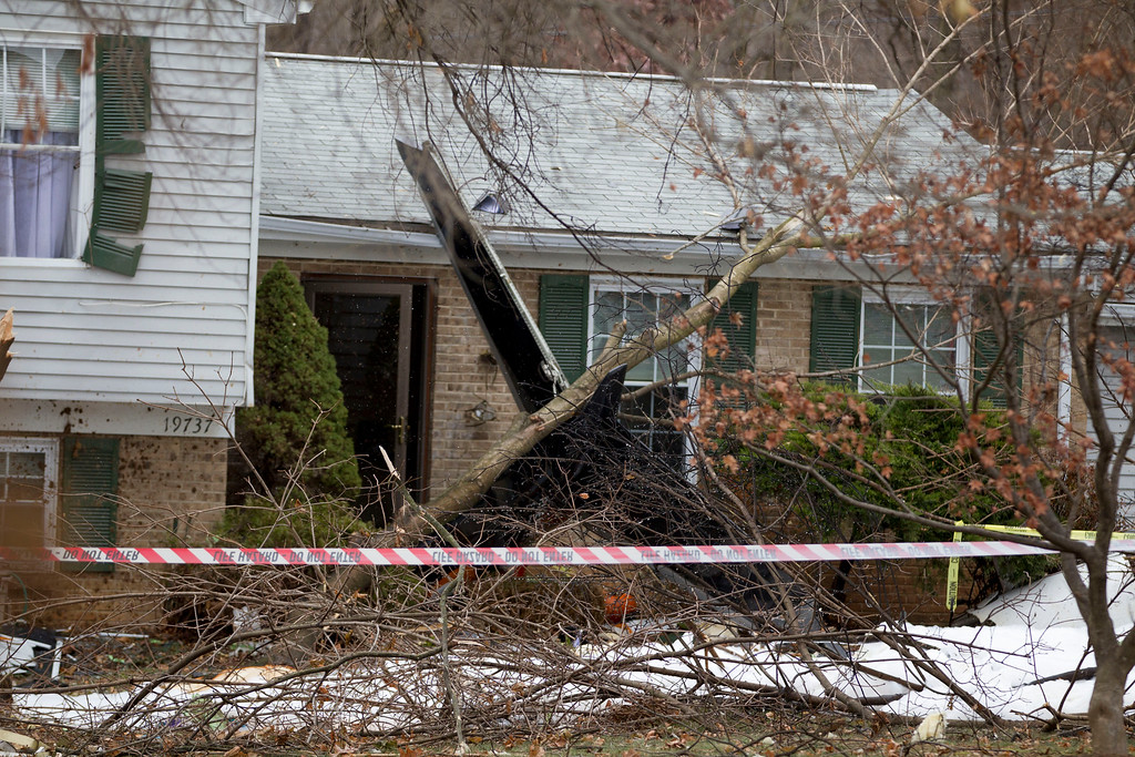 . The wreckage of a small private jet sits in a driveway after crashing into a neighboring house in Gaithersburg, Md., Monday, Dec. 8, 2014. A woman and her two young sons inside the home and three people aboard the aircraft were killed, authorities said. (AP Photo/Jose Luis Magana)