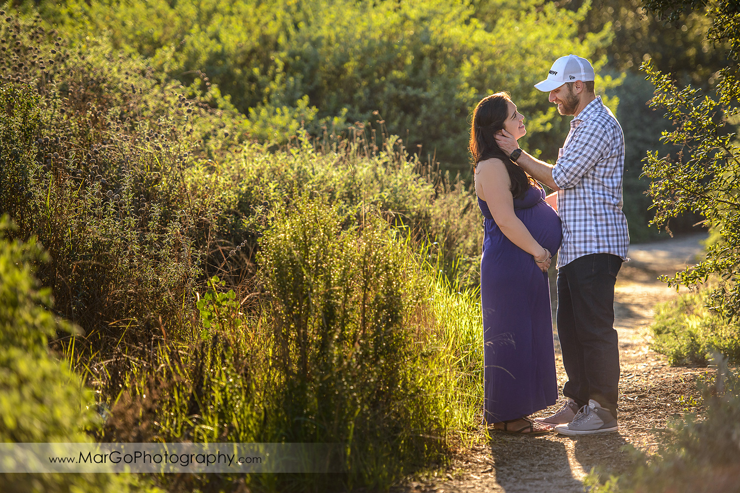man in checkered shirt and pregnant woman in long violet dress looking at each other during maternity session at Ulistac Natural Area in Santa Clara
