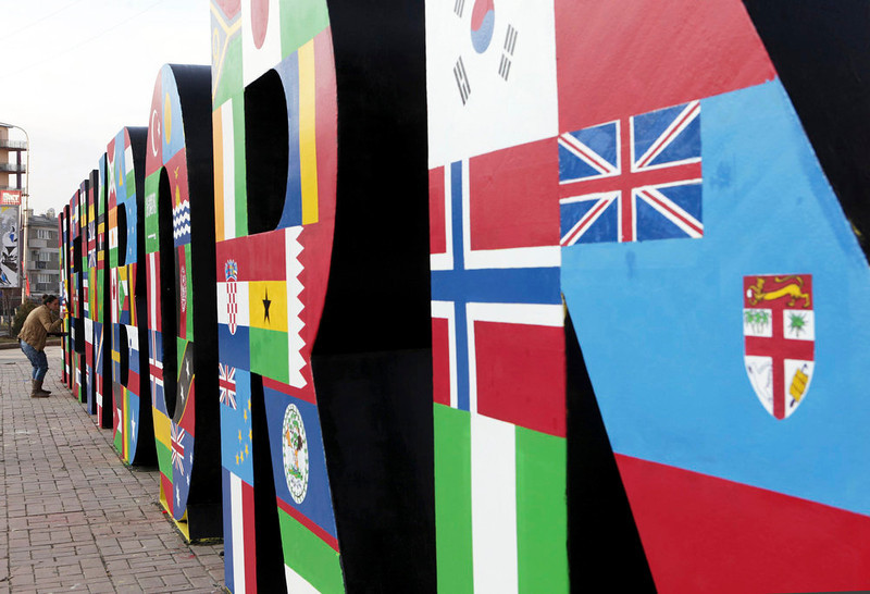 . A woman paints a sign decorated with paintings of flags of the 98 countries that have recognised Kosovo\'s independence, in Pristina February 17, 2013. Kosovo marks the fifth anniversary of its independence from Serbia on Sunday. REUTERS/Hazir Reka