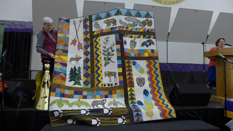 Linda Wells found a panel while visiting her daughter in Virginia.  She designed the quilt using the panel and added appliqué pieces to coordinate with the animals.  The quilt is for her husband.  Quilted by Kelly Sattler.