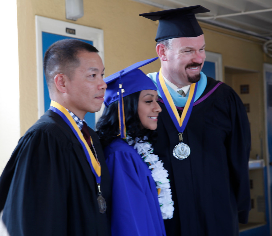 . Senior class sponsors, Mr. Jerry Lee and Mr. Sean King pose for a photo with Oksana Flores, who did the Presentation of Class Gift, during the graduation ceremony, at John H Francis Polytechnic High School, Sun Valley, Calif., June 7, 2013. Photo: Lynn Levitt.