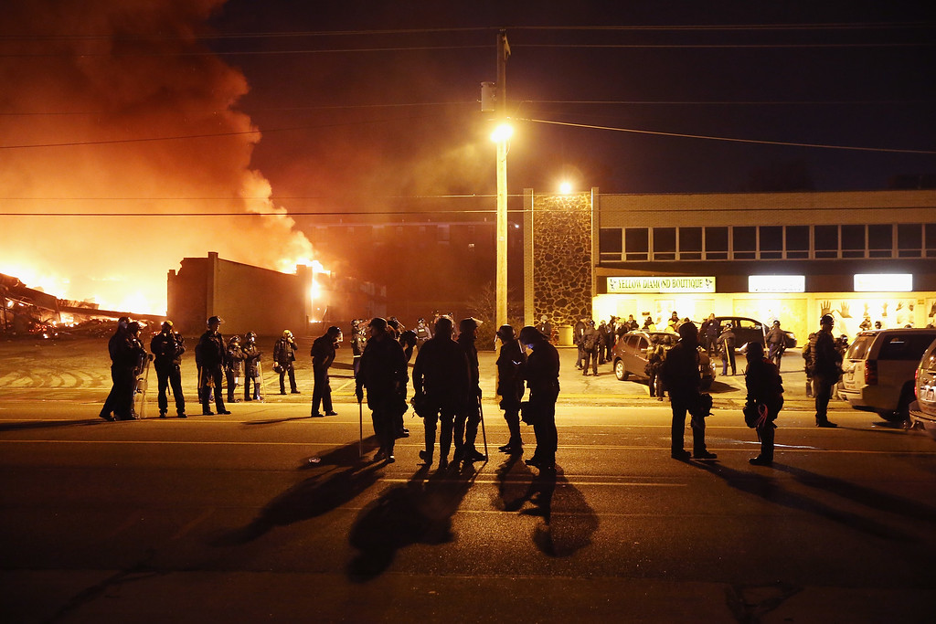. Police officers watch as a business burns after it was set on fire during rioting following the grand jury announcement in the Michael Brown case on November 24, 2014 in Ferguson, Missouri. Ferguson has been struggling to return to normal after Brown, an 18-year-old black man, was killed by Darren Wilson, a white Ferguson police officer, on August 9. His death has sparked months of sometimes violent protests in Ferguson. A grand jury today declined to indict officer Wilson.  (Photo by Scott Olson/Getty Images)