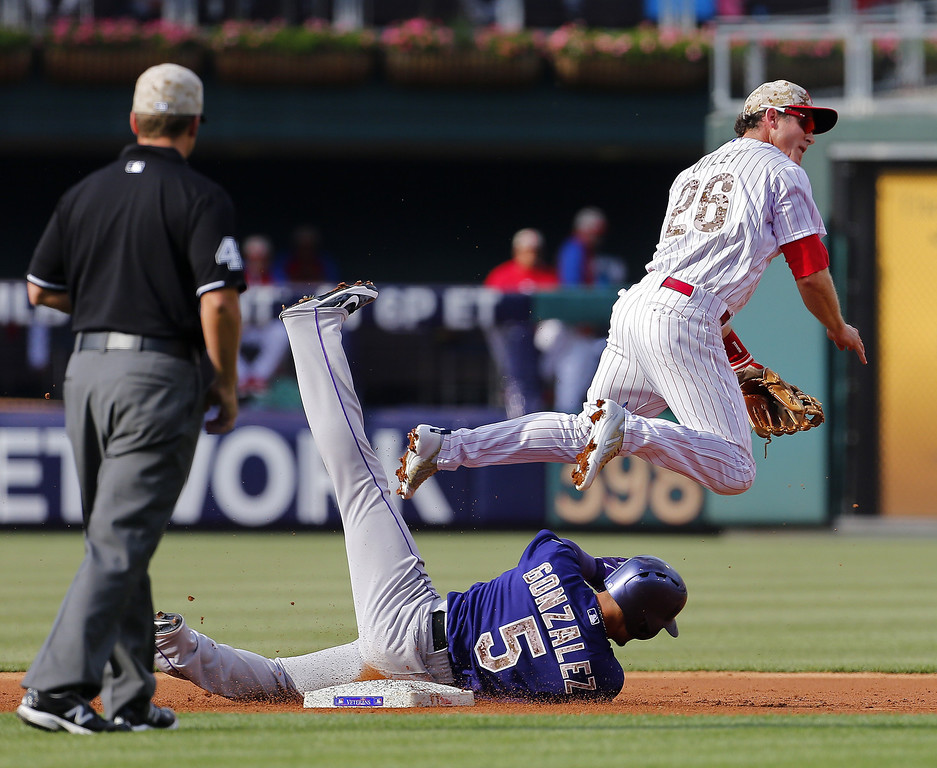 . Second baseman Chase Utley #26 turns a double play after forcing out Carlos Gonzalez #5 of the Colorado Rockies at second base in the second inning of a game at Citizens Bank Park on May 26, 2014 in Philadelphia, Pennsylvania. (Photo by Rich Schultz/Getty Images)