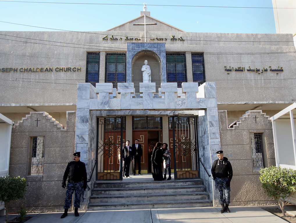 . Iraqi police officers guard the entrance of St. Joseph\'s Chaldean Church before a Christmas mass in Baghdad, Iraq, Wednesday, Dec. 25, 2013. Militants on Wednesday launched two separate attacks against Christians in Baghdad, officials said. There was no immediate claim of responsibility for the attacks, but Iraq\'s dwindling Christian community, which is estimated to number about 400,000 to 600,000 people, has often been targeted by al-Qaida and other insurgents who see the Christians as unbelievers.(AP Photo/Karim Kadim)