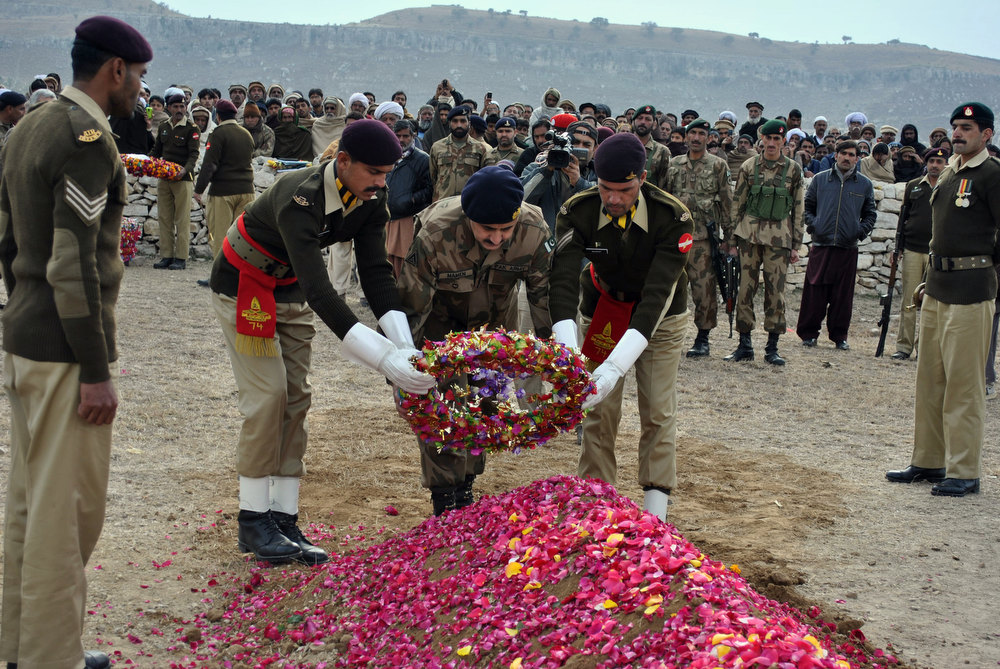 Description of . This photograph taken on January 8, 2013 Pakistani army officials lay a wreath on the grave of soldier Mohammad Aslam, who was killed during a border post attack in the Haji Pir sector of Pakistan-administered Kashmir by Indian soldiers, during his funeral in Khairpur village Chakwal district. Pakistani and Indian troops exchanged fire on January 6 along their hotly disputed border in divided Kashmir, with each side accusing the other of starting the clash. Pakistan on January 9 denied an Indian claim that its troops killed two Indian soldiers in a cross-border attack on January 8 that has raised tensions in South Asia, a military official said. AFP PHOTO/STRSTR/AFP/Getty Images