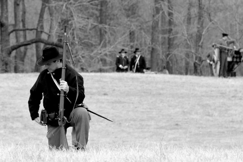 A Union infantry reenactor takes a knee in a single firing position while reloading his rifle. The Skirmish at Gamble's Hotel happened on March 5, 1885 when 500 federal soldiers, under the command of Reuben Williams of the 12th Indiana Infantry, marched into Florence to destroy the railroad depot but were met by Confederate soldiers backed up with 400 militia. The reenactment, held by the 23rd South Carolina Infantry, was held at the Rankin Plantation in Florence, South Carolina on Saturday, March 5, 2011. Photo Copyright 2011 Jason Barnette