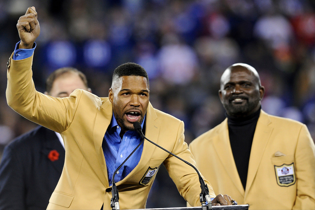 . Pro Football Hall of Fame defensive end Michael Strahan, left, speaks after he received his Hall of Fame Ring of Excellence as Lawrence Taylor watches him during a halftime ceremony of an NFL football game between the New York Giants and the Indianapolis Colts, Monday, Nov. 3, 2014, in East Rutherford, N.J.  (AP Photo/Bill Kostroun)