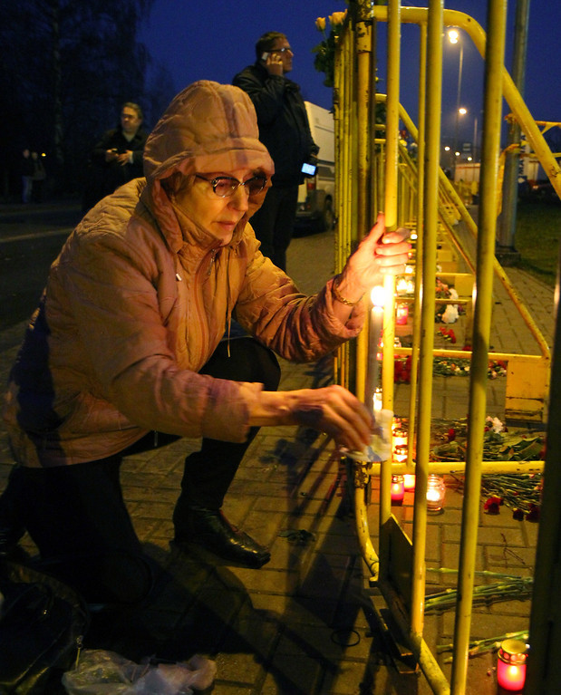 . A woman lights a candle near the collapsed shopping centre in Riga on November 22, 2013.   AFP PHOTO / PETRAS MALUKAS/AFP/Getty Images