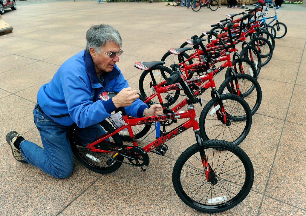. DENVER, CO - Oct. 11: Volunteer Tom Iskiyan makes adjustments to the bikes outside the Tabor Center downtown. Wish for Wheels and its volunteers build and give away over one hundred bikes to kindergarteners and first-graders at Smith Renaissance School in Park Hill. Wish for Wheels says its goal with one-in-five children liven in poverty, is to give as many kids as possible their first brand new bike and helmet. (Photo By Kathryn Scott Osler/The Denver Post)