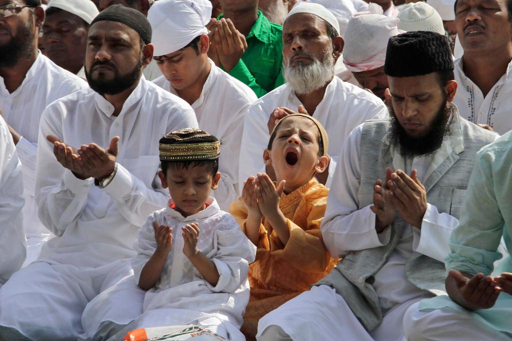 . A boy yawns as Indian Muslims offer prayers during Eid al-Adha, or the Feast of the Sacrifice, in  Kolkata, India, Wednesday, Oct. 16, 2013. (AP Photo/Bikas Das)