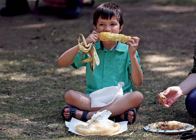 Caleb Piñeda-Sena, 6, eats sweet corn in the plaza during the 306th Fiestas de Santa Fe at the Plaza on Friday, September 6, 2019. Luis Sánchez Saturno/The New Mexican