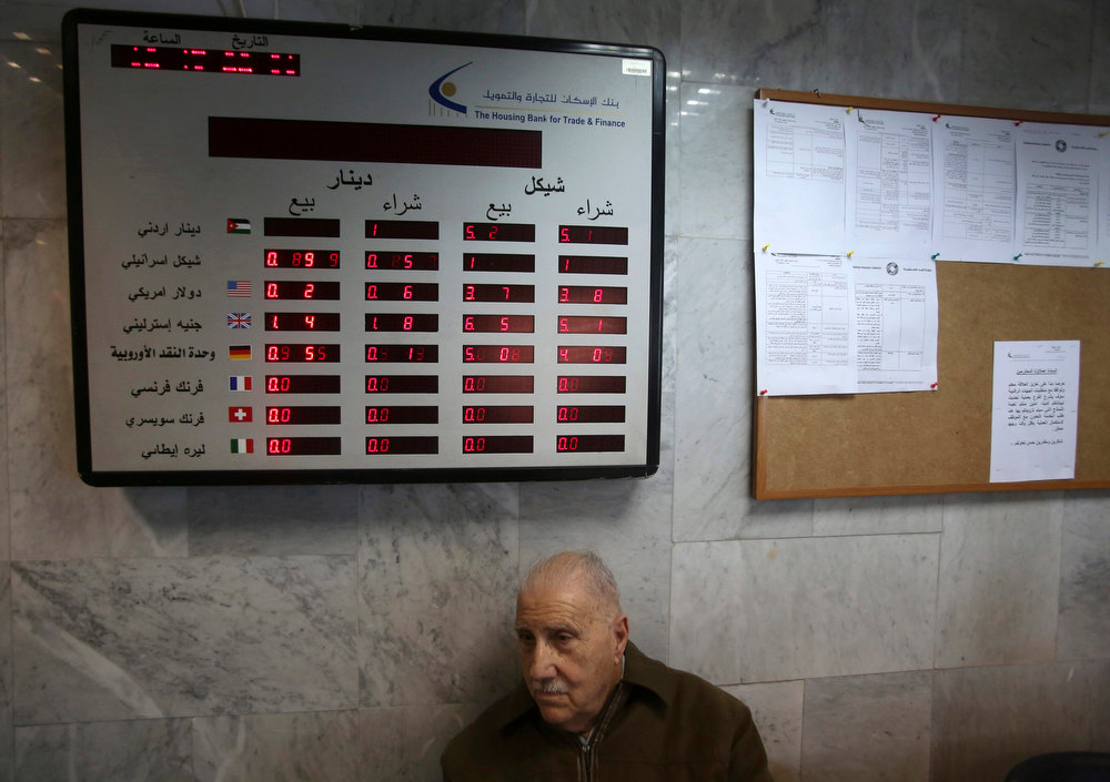 Description of . A Palestinian man sits under an electronic board displaying currency exchange rates at the Housing Bank for Trade & Finance in the West Bank city of Ramallah January 22, 2013. A central bank in the making, the Palestine Monetary Authority (PMA) is a rare bright spot as the economy of the Palestinian territories struggles with Israeli sanctions. Enforcing on Palestinian banks a regimen of conservative lending that has kept bad loans minimal and guaranteed liquidity, the PMA's technocratic prowess is the pinnacle of a Palestinian drive to build institutions fit for a future state. Picture taken January 22, 2013. REUTERS/Mohamad Torokman