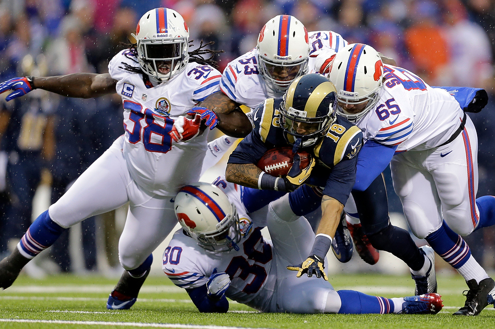 . St. Louis Rams punt returner Austin Pettis (18) is tackled by Buffalo Bills players Corey McIntyre (38), Nigel Bradham (53), Garrison Sanborn (65) and Mana Silva (30) during the second half of an NFL football game, Sunday, Dec. 9, 2012, in Orchard Park, N.Y. The Rams won 15-12. (AP Photo/Gary Wiepert)