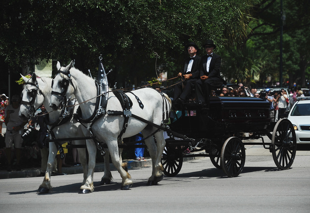 . Sen. Clementa Pinckney\'s remains arrive by horse drawn carriage at the South Carolina Statehouse, Wednesday, June 24, 2015, in Columbia, S.C. Pinckney\'s open coffin was being put on display under the dome where he served the state for nearly 20 years. Pinckney was one of those killed in a mass shooting at the Emanuel AME Church in Charleston. (AP Photo/Rainier Ehrhardt)