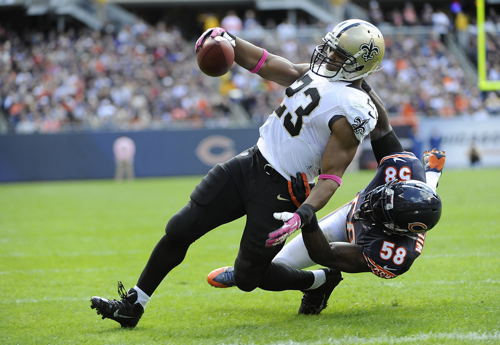 . Pierre Thomas #23 of the New Orleans Saints catches a touchdown pass as he\'s defended by D.J. Williams #58 of the Chicago Bears during the second quarter on October 6, 2013 at Soldier Field in Chicago, Illinois. (Photo by David Banks/Getty Images)