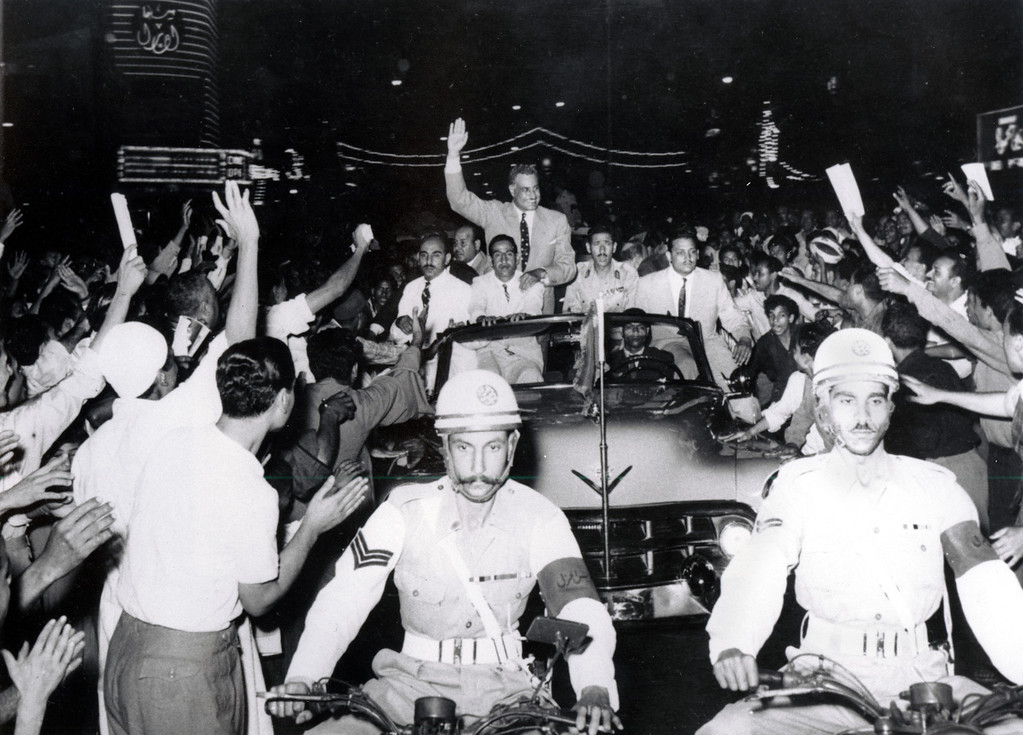 . Egyptian Premier Gamal Abdel Nasser waves to a crowd of people as he stands in an open car moving through the streets of Cairo, Egypt on June 19, 1956.  Nasser announced at a rally in Republican Square that martial law in Egypt is ended, that the revolution council which has ruled Egypt since King Farouk was deposed is dissolved, that Egypt\'s new constitution will be ratified and that a new president will be elected.  (AP Photo)