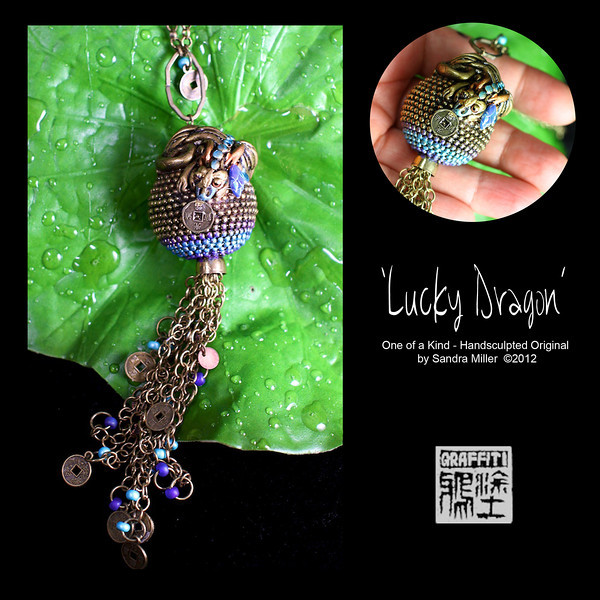 """LUCKY DRAGON-  CLICK HERE TO VIEW VIDEO DESCRIPTION IN A NEW WINDOW   OOOOH this is a stunner!!!.  If you love long sexy necklaces you will adore LUCKY DRAGON!!!  I started with a really awesome brass ball/fringed necklace I purchased on my travels. and handsculpted a yummy little dragon with REAL German glass eyes,  lying on top in polymer clay..his muzzle is nuzzling a replica Chinese Coin.    Once fired, I started applying real brass to the surface over the course of a few days until I had a thick coat to add my patina.  The blues, greens, and deep tones in the the grooves come from actually accelarating the aging process of the metals with acids and chemicals.  When the patina got to the perfect stage, I sealed the design to keep it exactly as it is today. Rich and opulent!!!!  From that point I got to have some fun by adding vintage flower bud cabochon under Mr Dragon's feet,  and then I went crazy with beadwork and replica Chinese coins on the tassel chain!!!  This design has so much swish and sway. She hangs just as the bustline drops off and the chain is adjustable to many lengths.  This length is my favorite to wear on tunics, Tshirts and turtlenecks as opera length necklaces are SO slenderizing!!!  This is a chance to wear a one of a kind brass necklace as the fraction of the weight and price of a solid brass design. The polymer clay base really keeps this light yet unbelievably sturdy as well.   PENDANT MEASURES 1 1/2 LONG PLUS 4"""" FRINGE   Chain is fully adjustable to 24"""" long"""