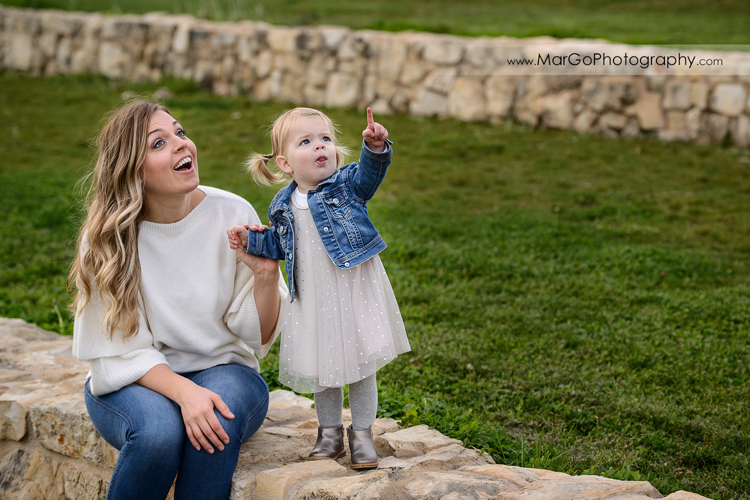 mother in white blouse and jeans and little girl in white dress and jeans jacket sitting on the stone wall during family session at San Jose Martial Cottle Park