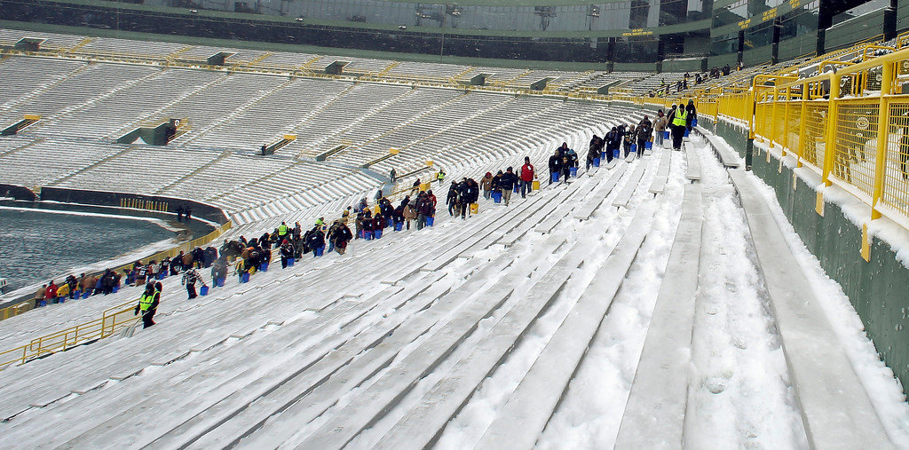 . Workers put down salt in the seating area of Lambeau Field before an NFL football game between the Green Bay Packers and the Pittsburgh Steelers Sunday, Dec. 22, 2013, in Green Bay, Wis. (AP Photo/Jeffrey Phelps)