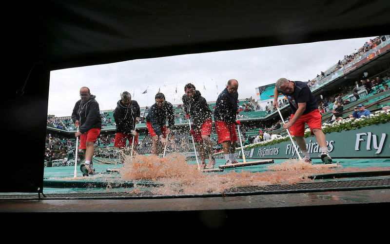 . Workers sweep water from a tarp covering a court during a rain delay at the French Open tennis tournament at the Roland Garros stadium in Paris May 28, 2013.   REUTERS/Stephane Mahe